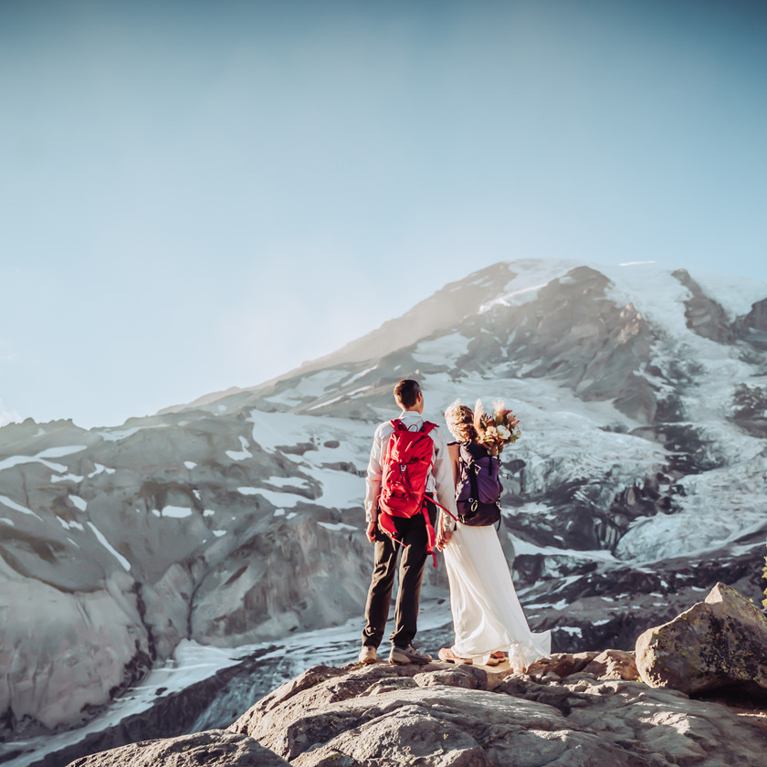 A couple in wedding attire with hiking backpacks on standing on a rock looking onto Mount Rainier