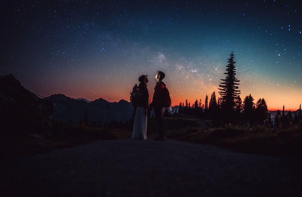 Bride and groom standing under the stars with headlamps on for their Mt. Rainier Elopement