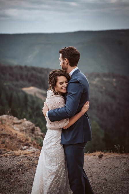 A bride and groom hugging on top of a mountain pass on their wedding day in Nevada City, California