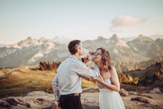 Bride and Groom drinking champagne on top of a mountain for their Mt. Rainier Elopement