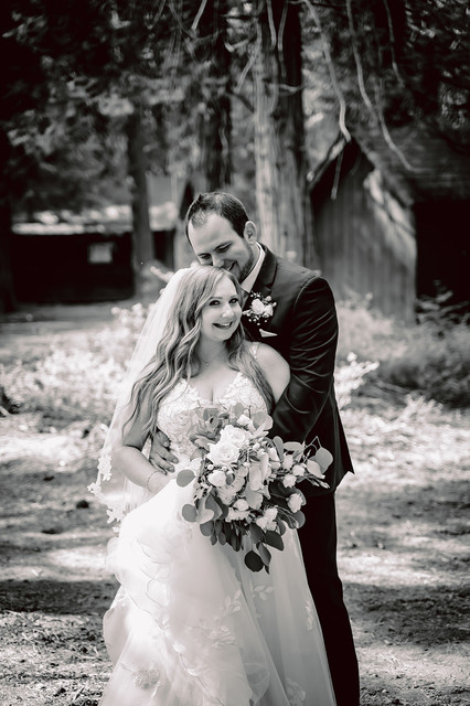 A black and white of a groom holding his bride from behind and kissing her head
