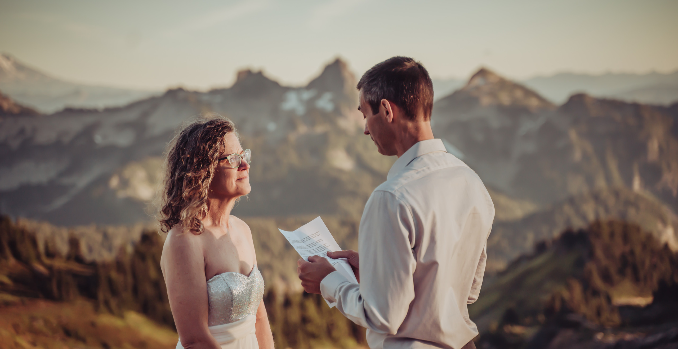 Groom reading his vows at his Mount Rainier Elopement with a backdrop of the mountains surrounding Mt. Rainier