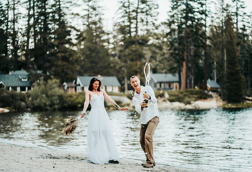 Groom spraying a bottle of champagne and bride reacting.  Backdrop in the lake and the lake cabins of Lake Tahoe.  Photo is showing Eloping in Lake Tahoe