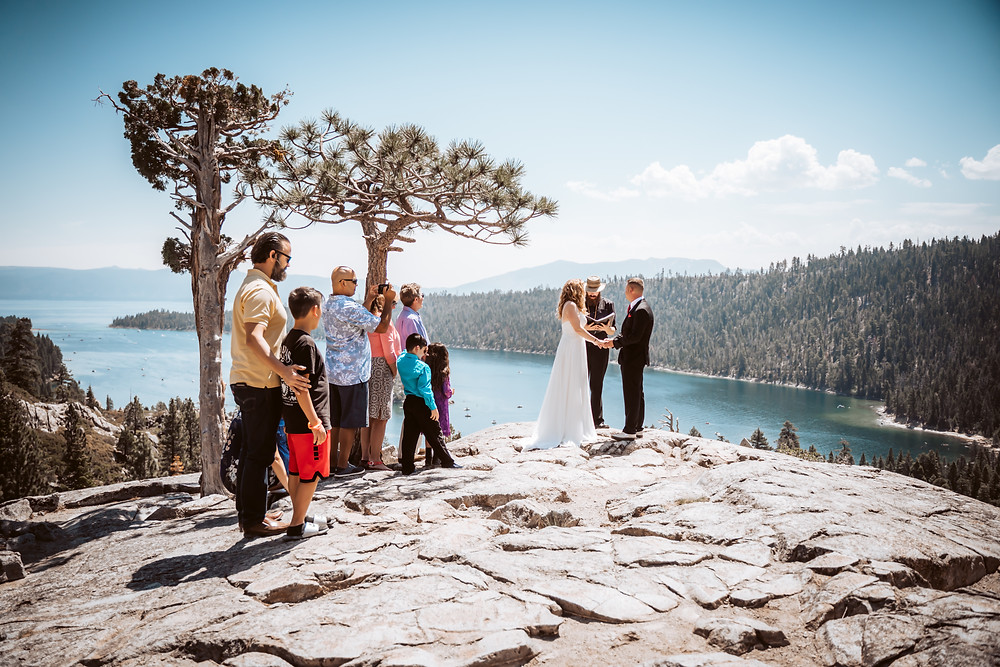 A wedding ceremony with a couple and the officiant and a few family members overlooking emerald bay in Lake Tahoe for their Lake Tahoe Elopement