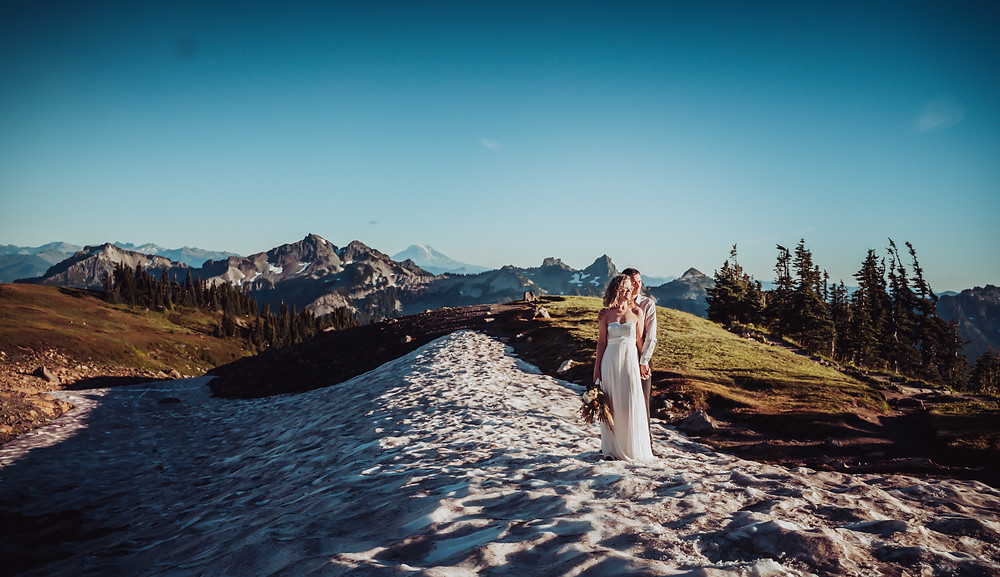 Bride and Groom standing on the snow covered mountain of Mt. Rainier for a Mt. Rainier adventure hiking elopement