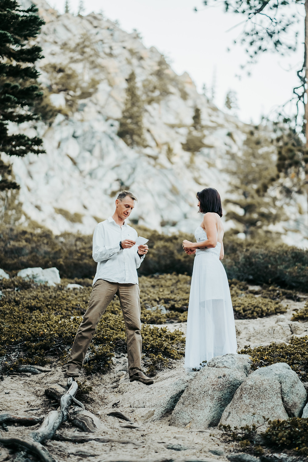 Bride and Groom reading vows in front of each other in front of a mountain backdrop in the mountains of Lake Tahoe.   Photo showing eloping in Lake Tahoe