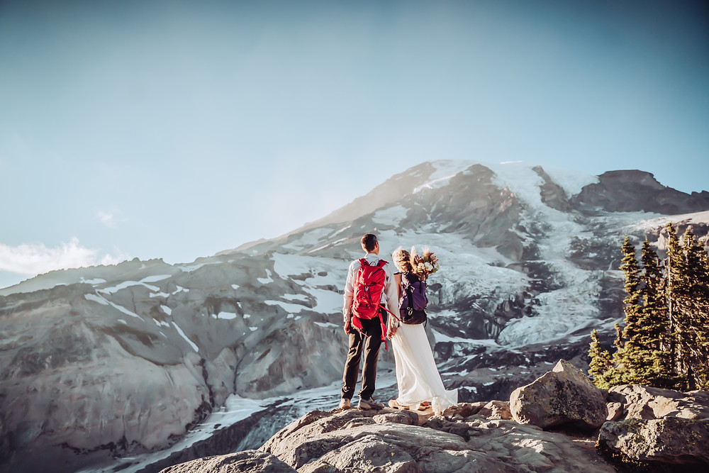A wedding couple in with hiking gear on overlooking Mt. Rainier for their elopement day
