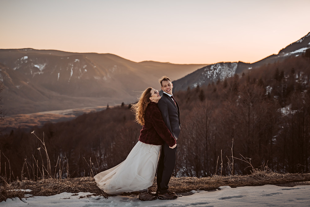 A bride standing behind her groom looking up at him in front of a mountain sunset for their Mt. St. Helens elopement