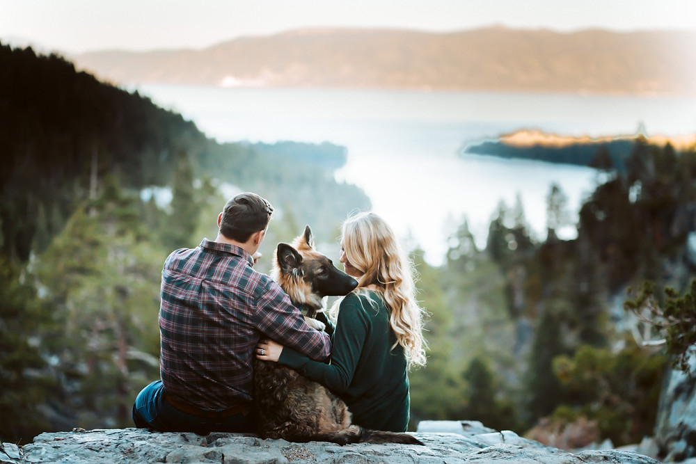 A couple and their dog looking out onto Emerald Bay in Lake Tahoe