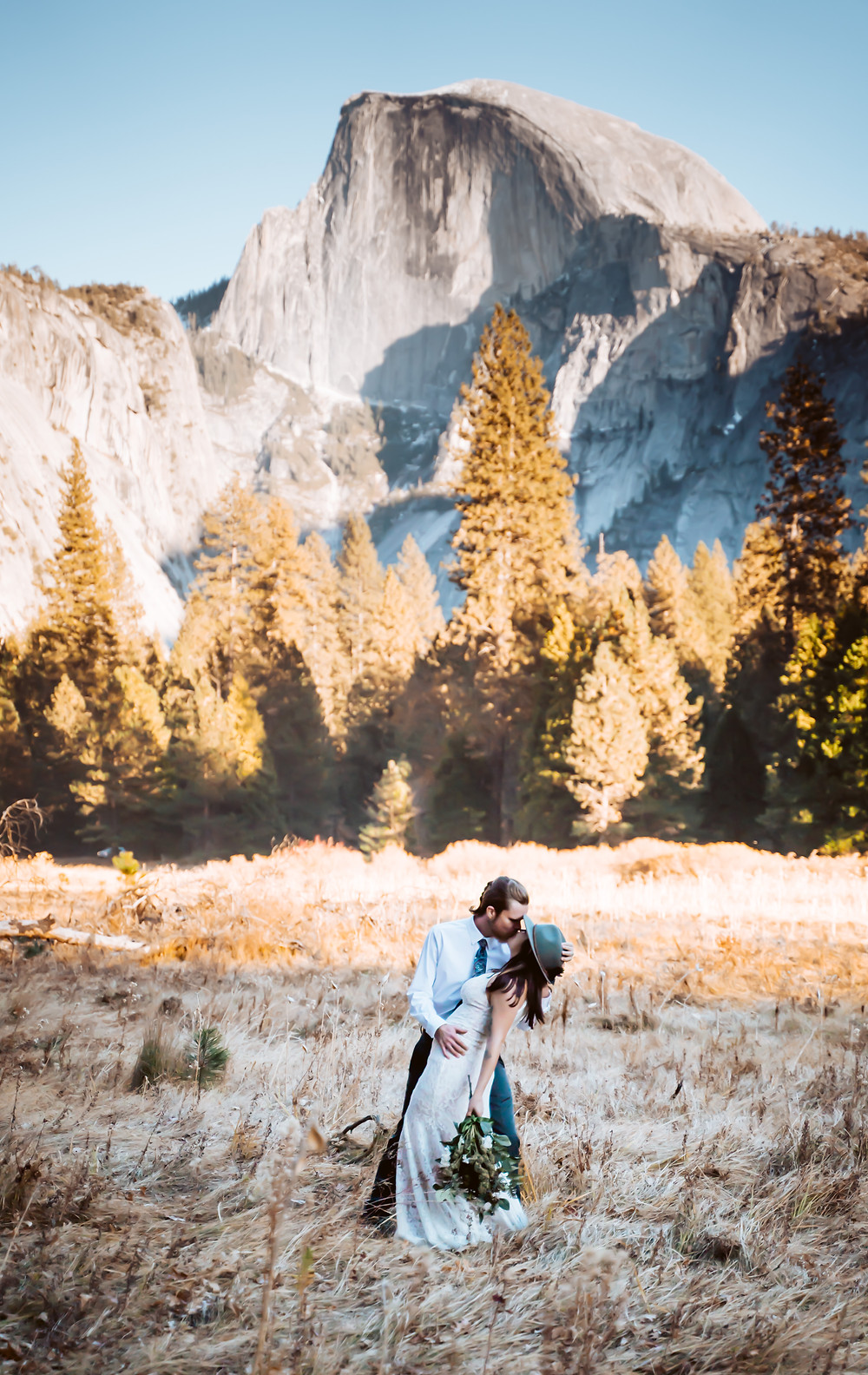 Bride and groom kissing in front of half dome in Yosemite National Park for their Yosemite elopement