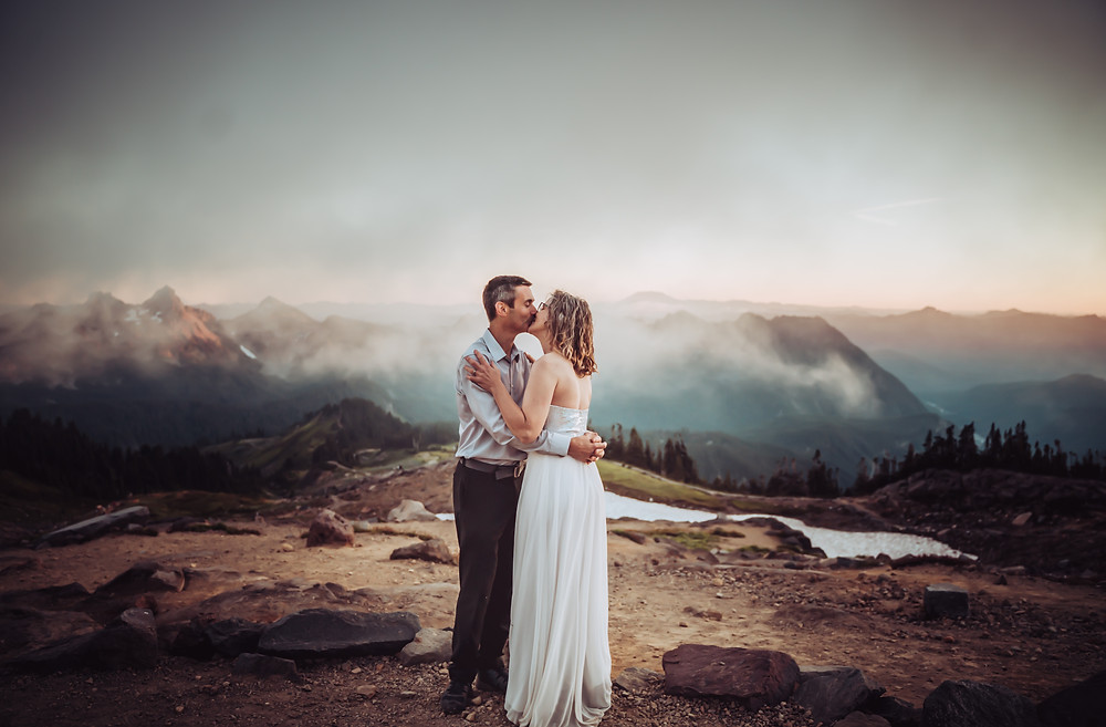 A bride and groom kissing in front of a mountain sunset at Mount Rainier