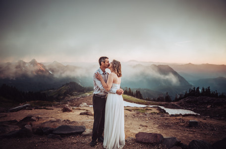 Bride and groom kissing in front of a mountain sunset at Mt. Rainier for their elopement