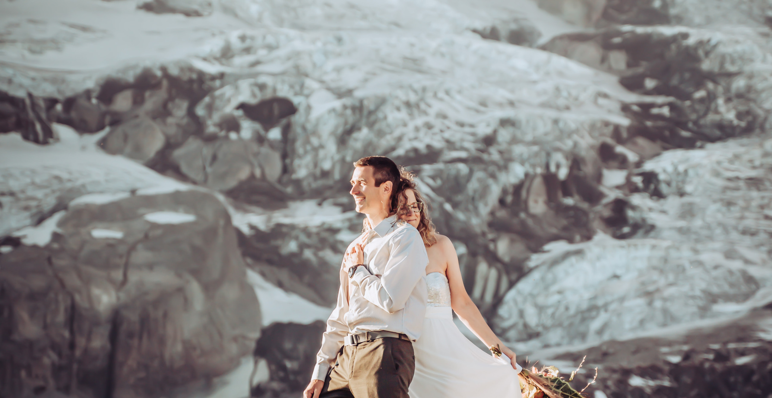 Bride holding the groom from behind looking out into the sunset with hiking boots on and Mt. Rainier in the background