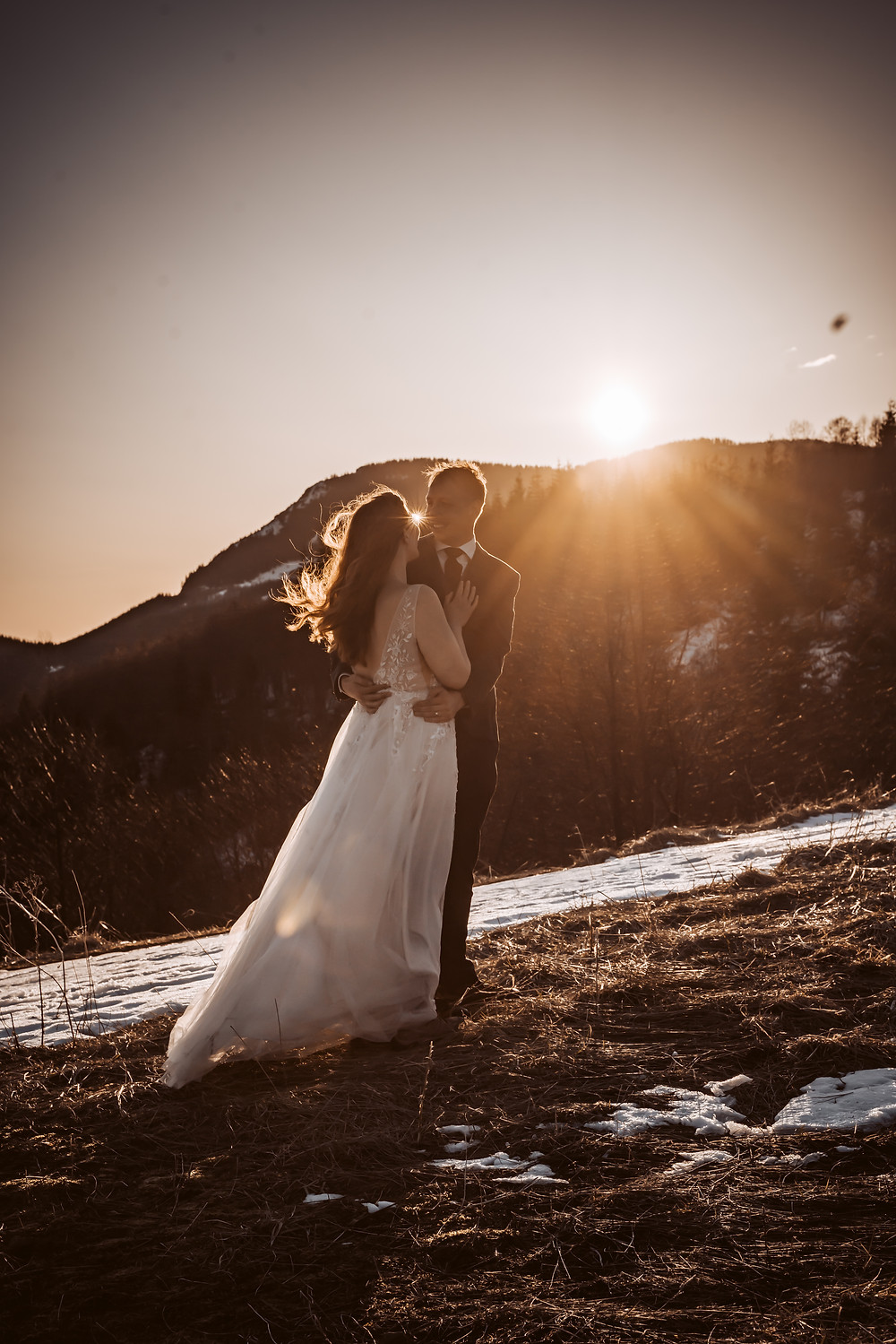 A bride and groom standing in front of the sun going down holding each other in front of the mountain backdrop in Mt. St. Helens