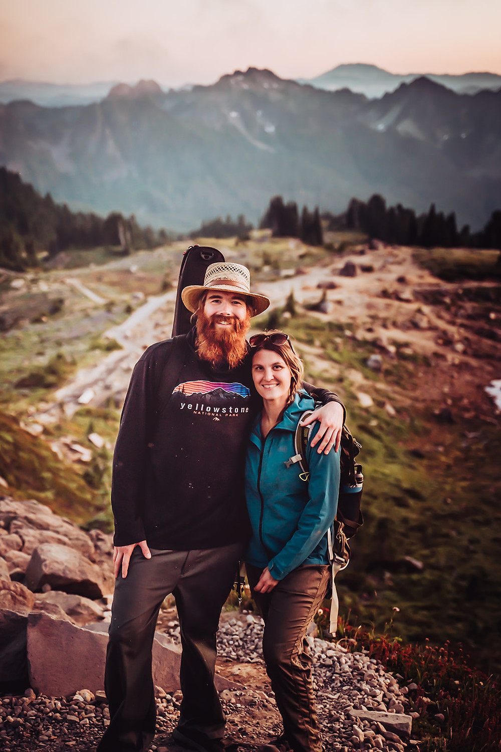 A elopement photographer and videographer team hiking in the mountains for an adventure wedding
