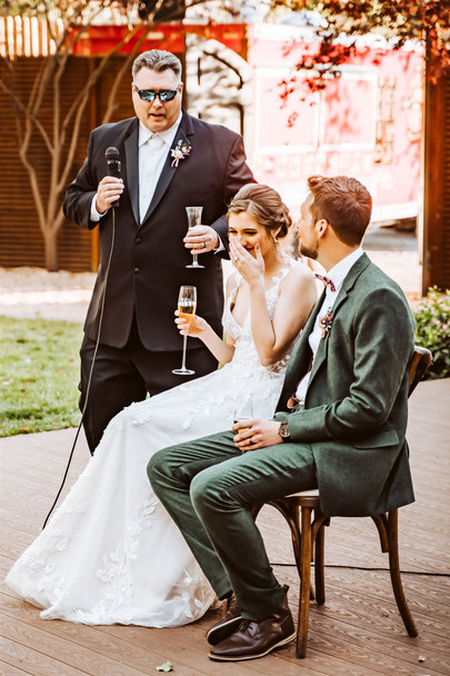A father giving his speak during the wedding and the bride laughing