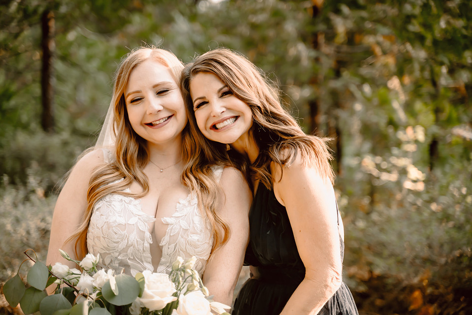 A bride and her mom smiling for pictures on her wedding day