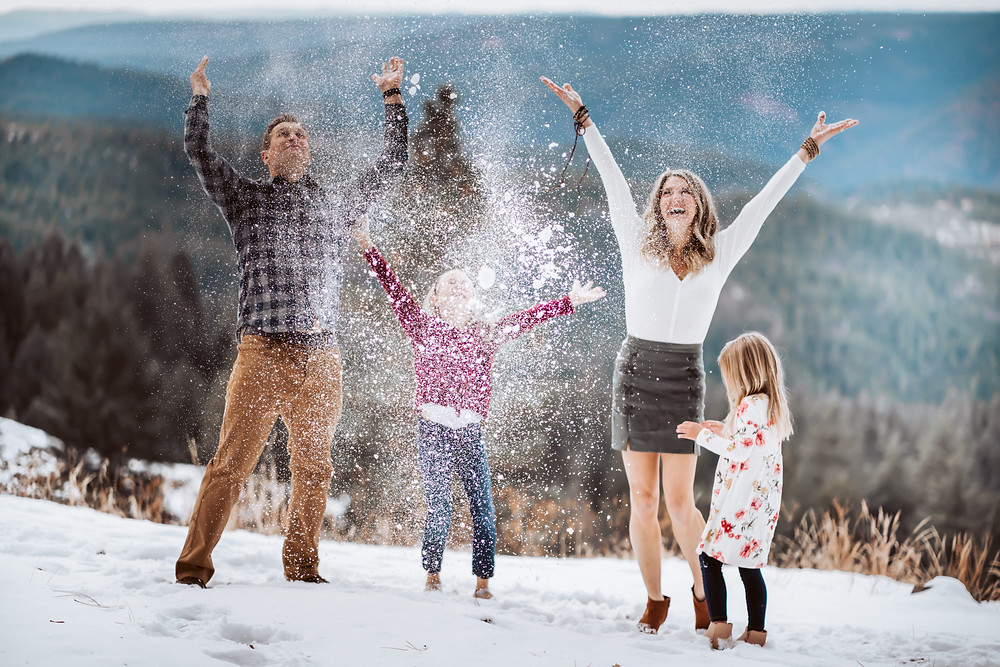 A family throwing snow up in the air for a family photo shoot in the snowy mountains