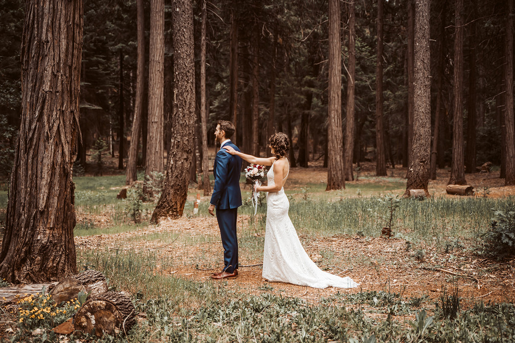 A bride getting ready for first look in the forest behind harmony Ridge Lodge in Nevada City California for their wedding day