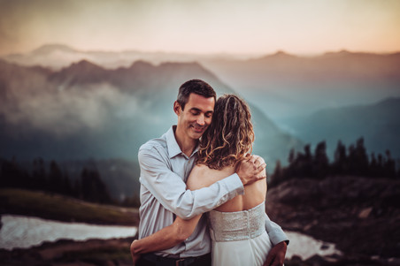 Bride and groom hugging in front of a mountain sunset