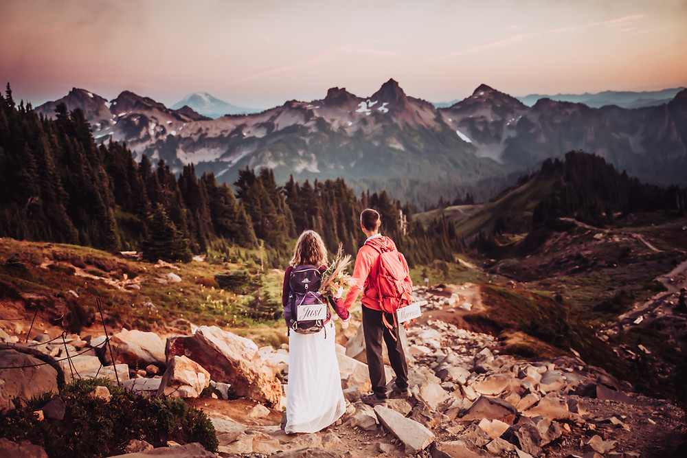Bride and Groom wearing hiking backpacks looking onto the mountain range at Mount Rainier at Sunset