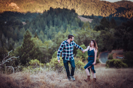 A couple walking in a field with the mountain landscape in the backdrop during their Mini Moon Photoshoot in Northern California