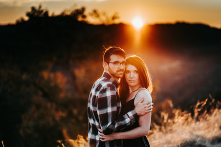 A couple embracing with the mountain sunset in the background during their Mini Moon Photoshoot in Northern California
