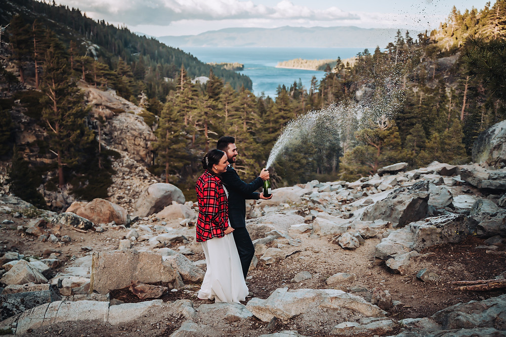 A wedding couple popping a bottle of champagne at sunset overlooking their elopement in Lake Tahoe at Emerald Bay