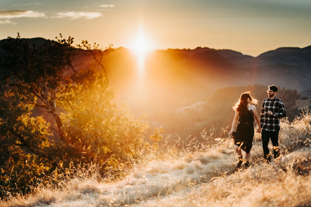 A couple walking down the trail with a mountain sunset in the background during their Mini Moon Photoshoot in Northern California