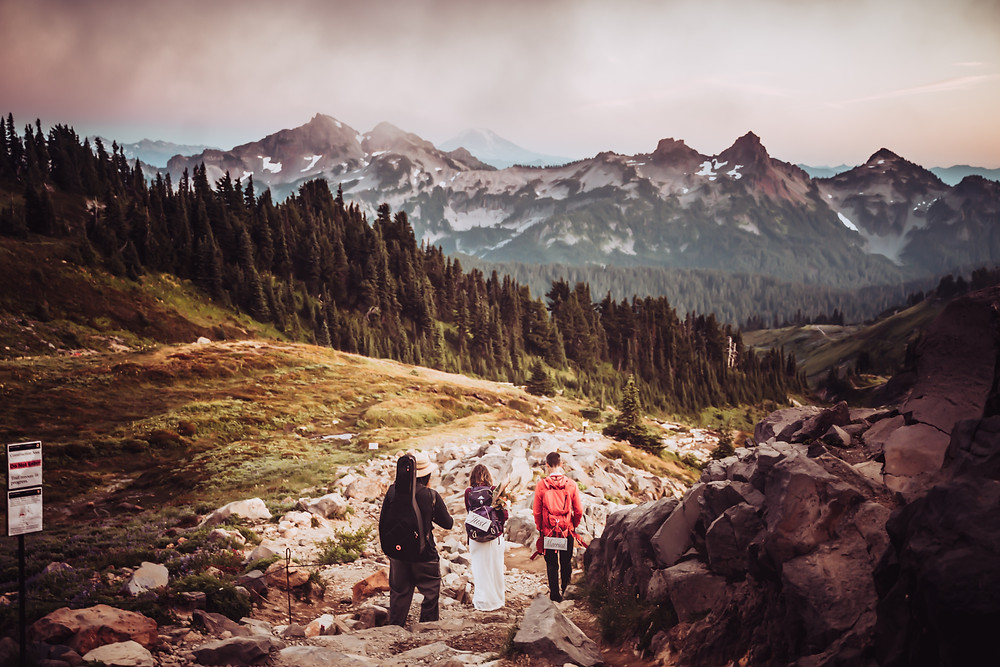 A couple in wedding dress and hiking backpacks hiking down Mount Rainier
