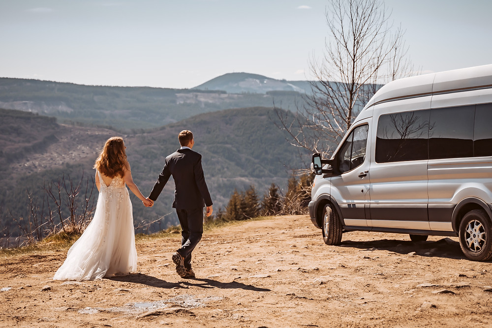 A bride and groom walking to their sprinter van in front of the mountains