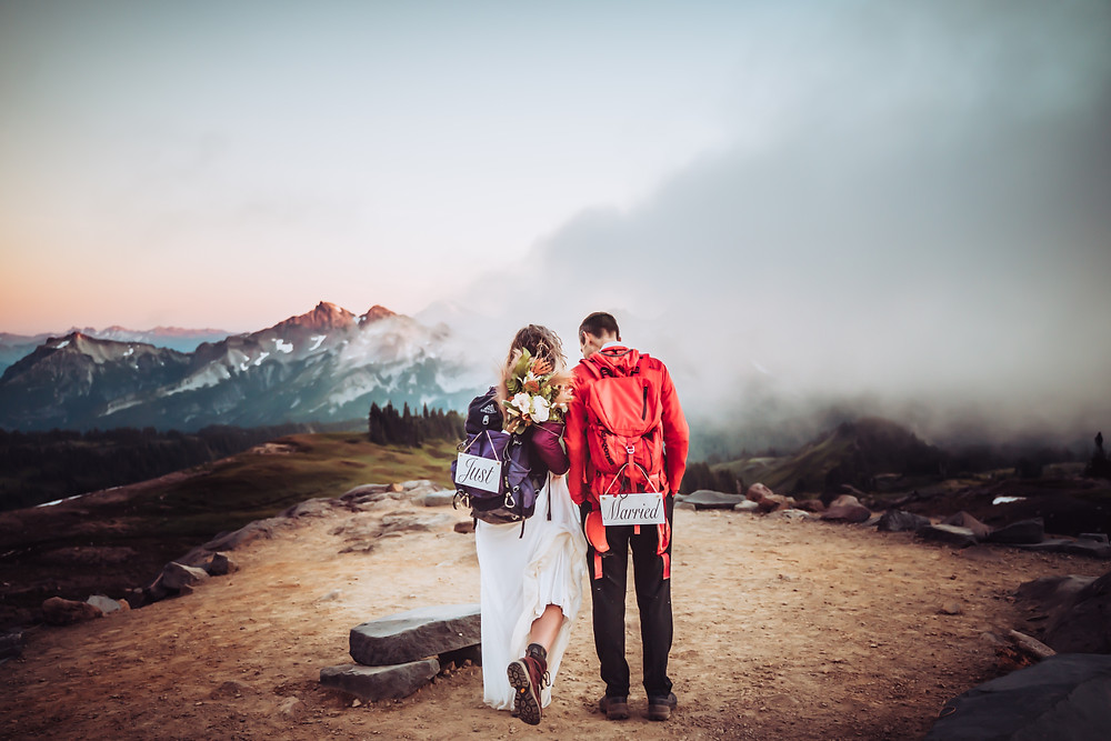 Bride and groom with hiking backpacks on that have signs hanging from the back that say Just Married.  With a mountain backdrop at Mt. Rainier