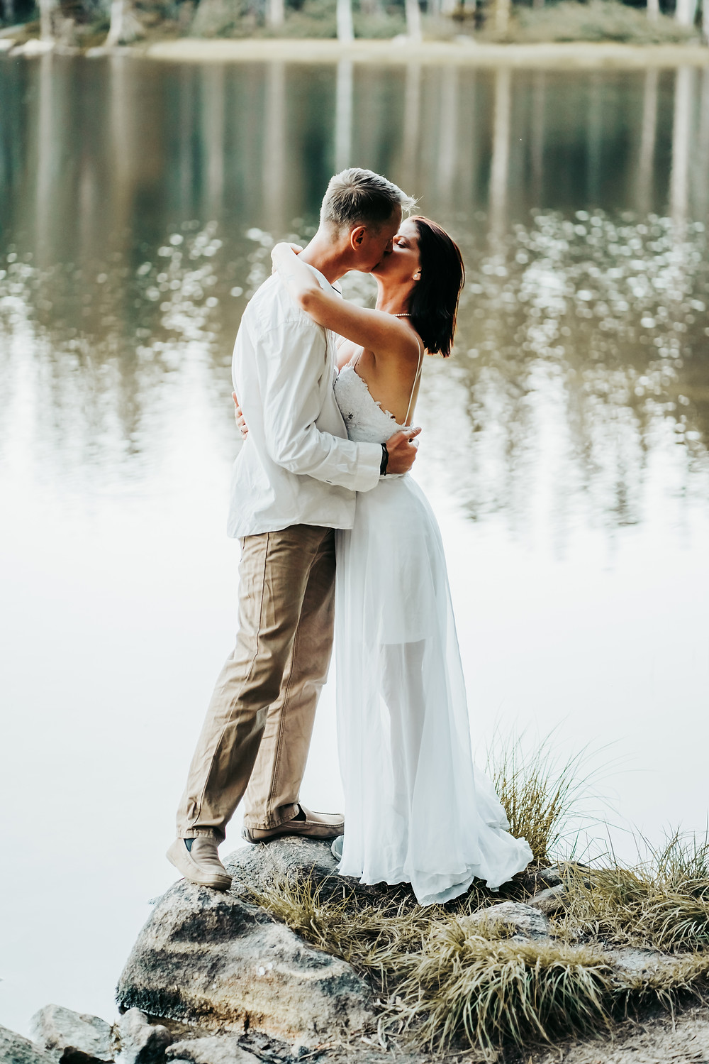 Bride and Groom kissing in front of a glistening lake.  Couples photos of eloping in Lake Tahoe