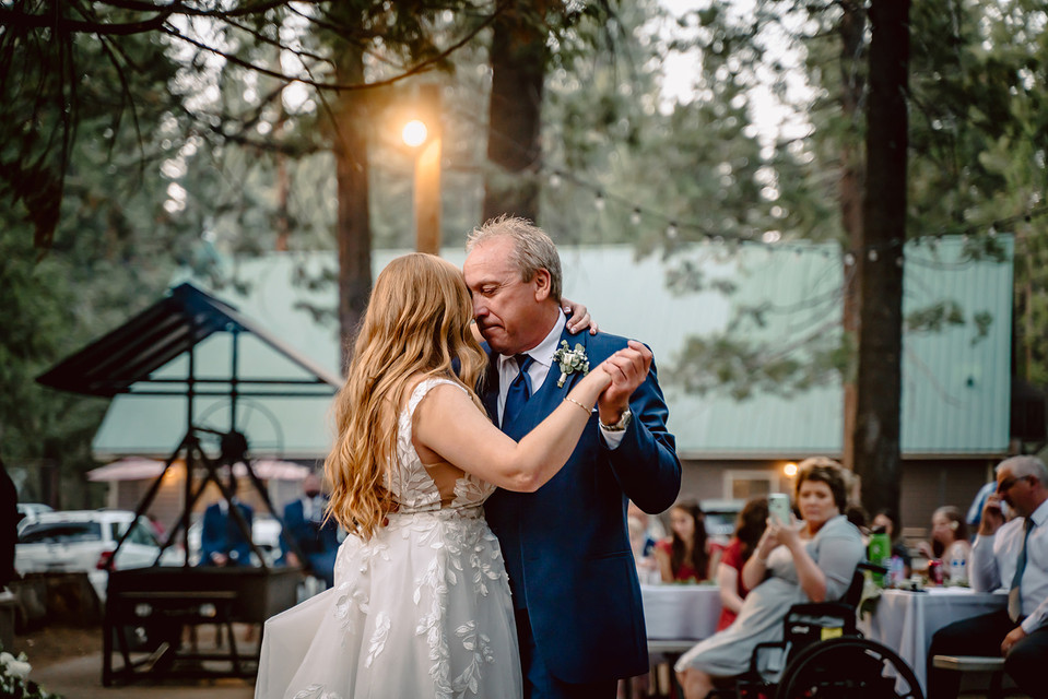 A bride and her father dancing to their first dance song at her wedding at Camp Sylvester in Pinecrest, California