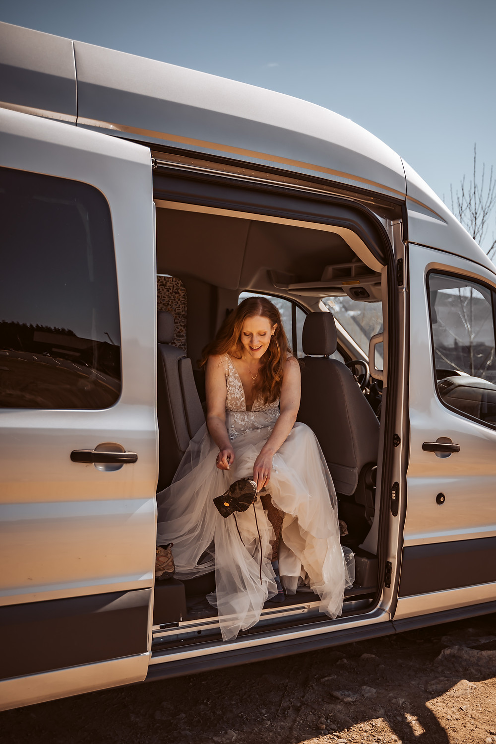 A bride putting on her hiking shoes in her wedding dress in her conversion van getting ready for her Mt. St. Helens elopement