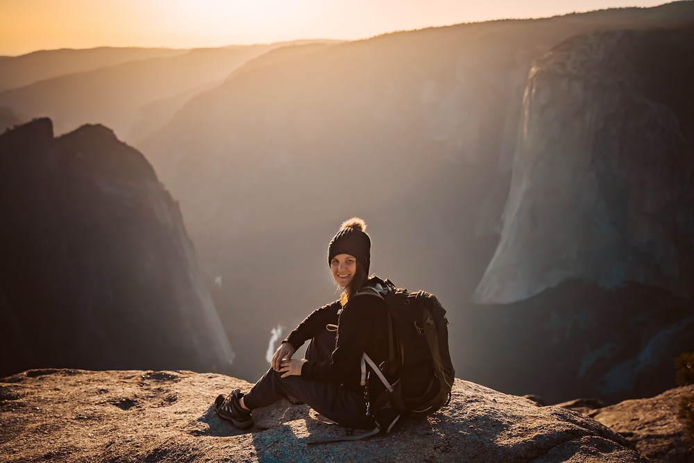 A elopement photographer wearing a hiking backpack sitting on a rock overlooking the sunset on the top of Yosemite Valley