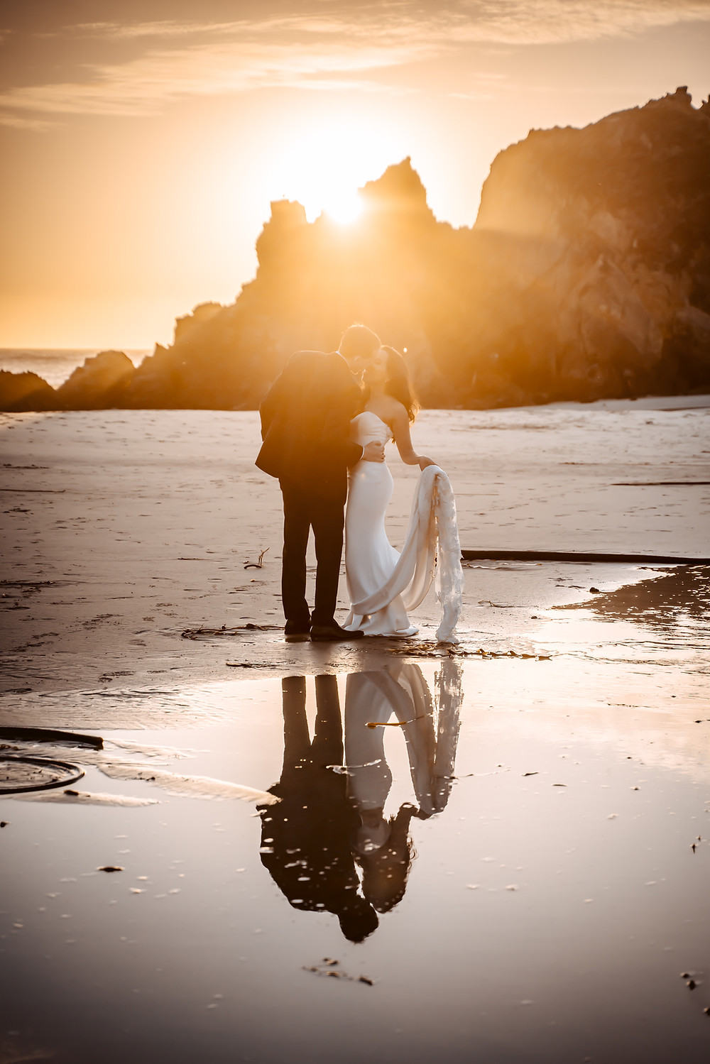 A bride and groom kissing on the beach during sunset in front of a reflection in a pond in Big Sur