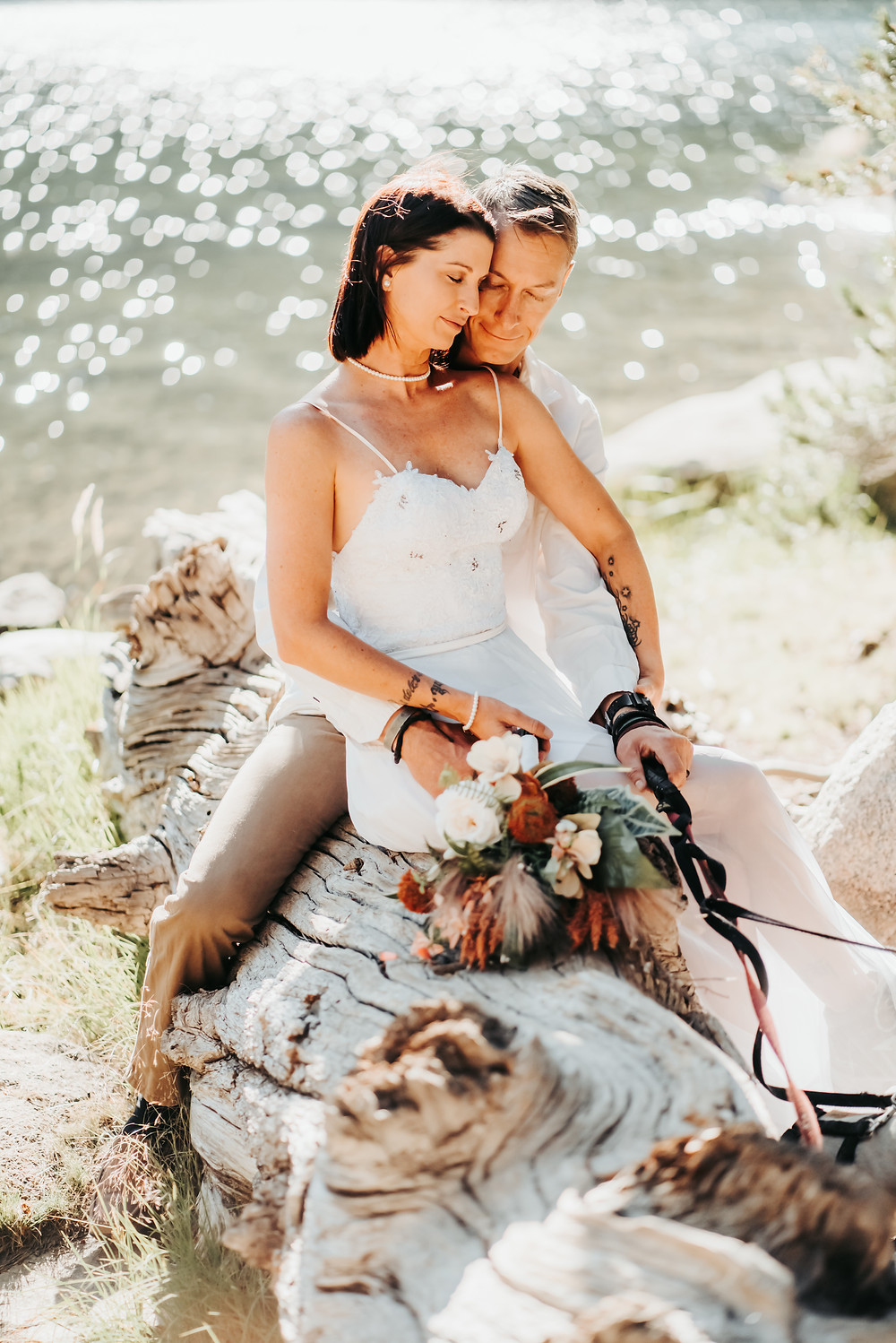 Bride sitting on Grooms lap on a dead tree next to a shimmering lake.  Their eyes are closed and look completely relaxed.  Photo is capturing eloping in Lake Tahoe