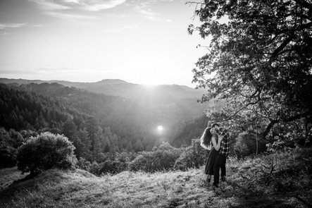 Black and White mountain landscape sunset with a couple embracing in a field during their mini moon photos shoot in Northern California