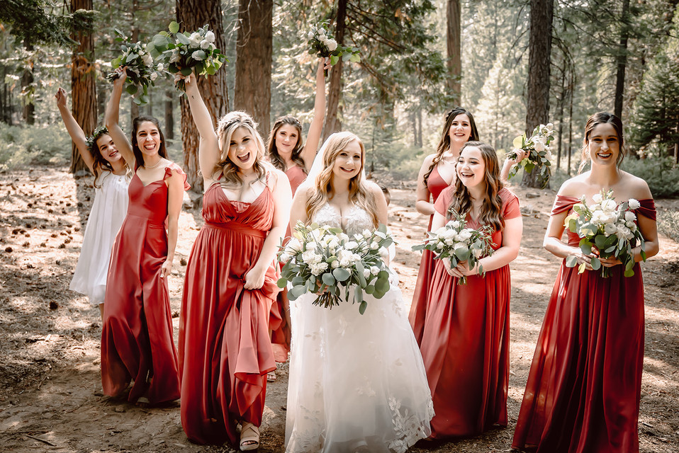 A bride and her bridal party walking through the forest at Camp Sylvester in Pinecrest, California for her wedding day