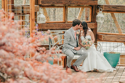 A bride and groom looking into each others eyes sitting on a bench with a beautiful wooden display in the backdrop