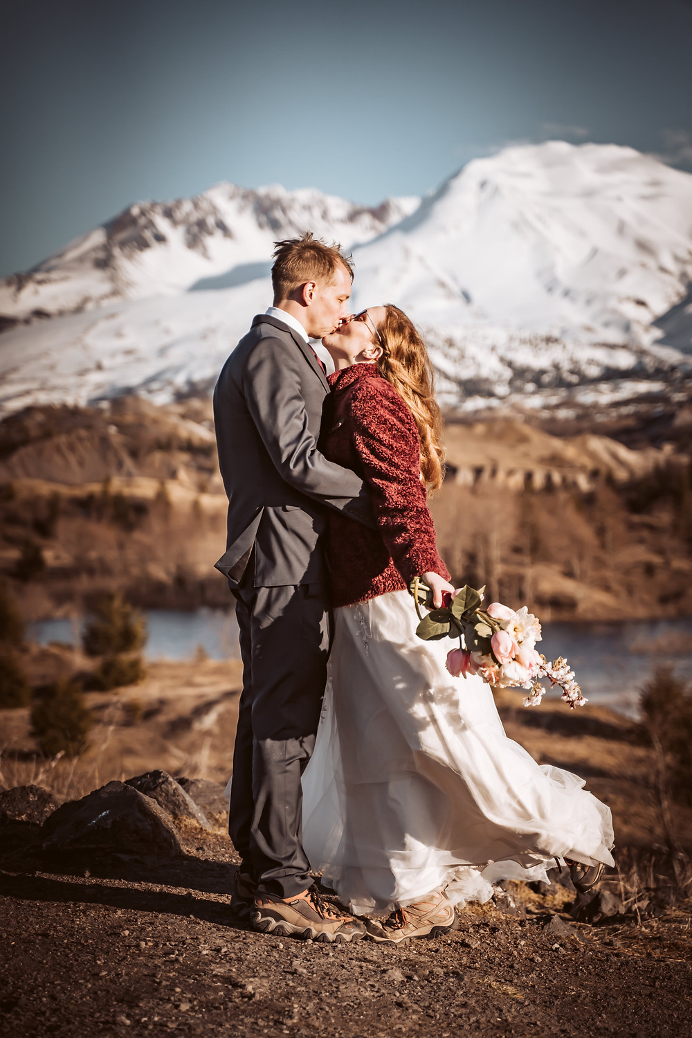 A bride and groom kissing in front of Mt. St. Helens for their elopement day