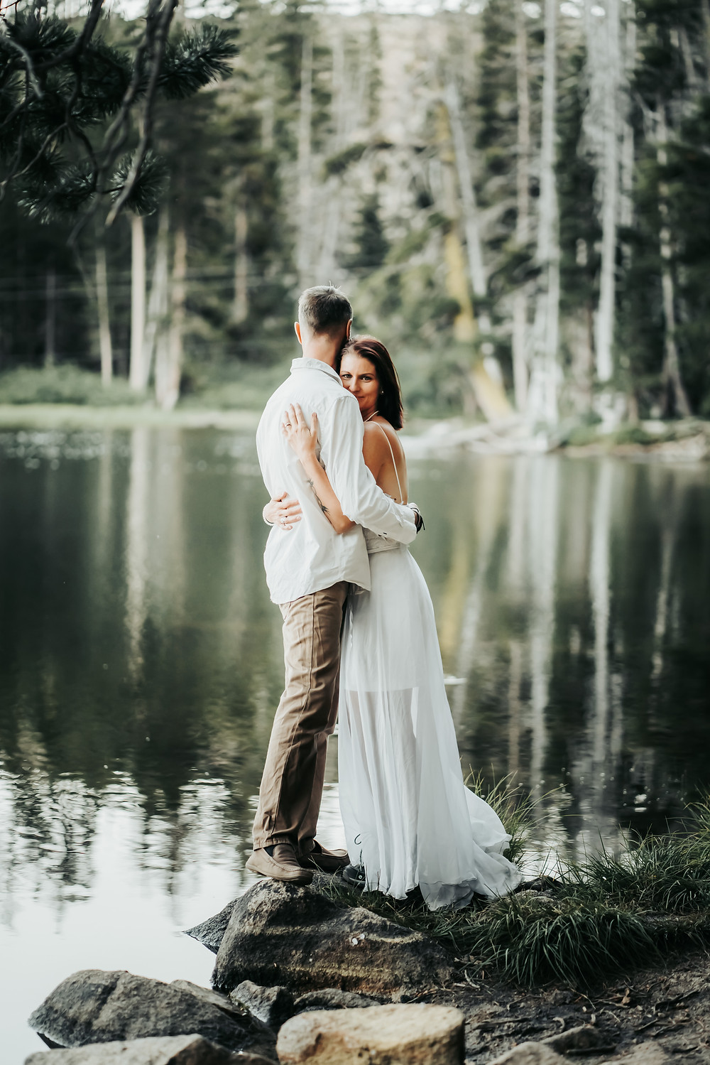 Bride and Groom embracing in front of a beautiful lake with a reflection backdrop.  Photos are of eloping in Lake Tahoe