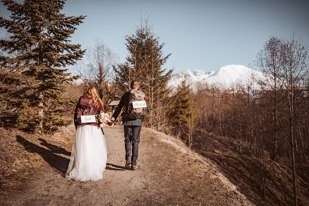 A bride and groom hiking in their wedding attire with hiking backpacks that have signs that say Just Married overlooking Mt. St. Helens Mountain