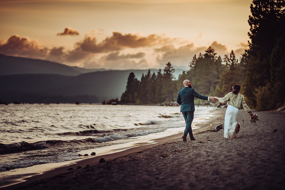 A bride and groom walking on Kings beach during sunset at Lake Tahoe for their elopement day.  One of the best places to elope in Lake Tahoe