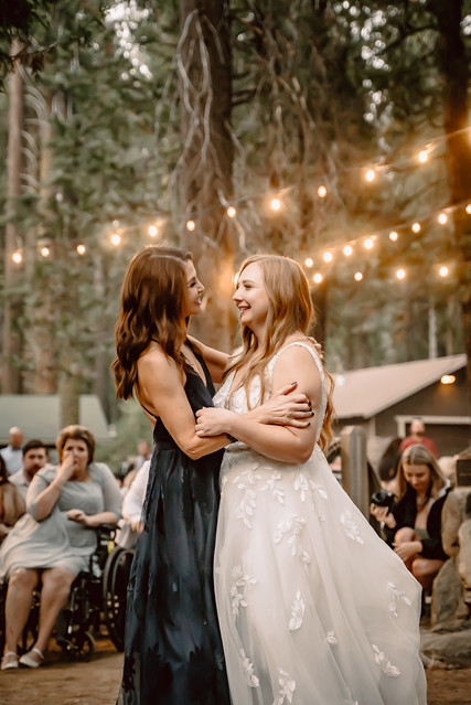 A bride and her mom dancing under twinkling lights in the forest for a outdoor wedding reception at Camp Sylvester