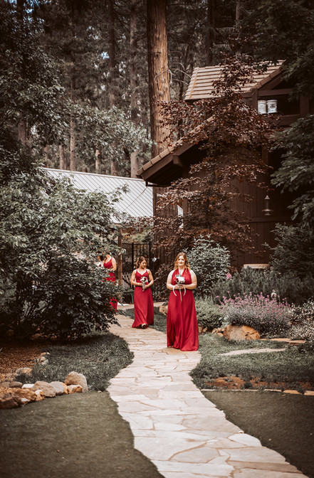 The bridal party entering their ceremony in red dresses with the forest as their backdrop