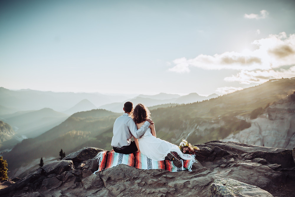 Bride and Groom sitting on a mountain blanket looking out onto the sunset at Mount Rainier