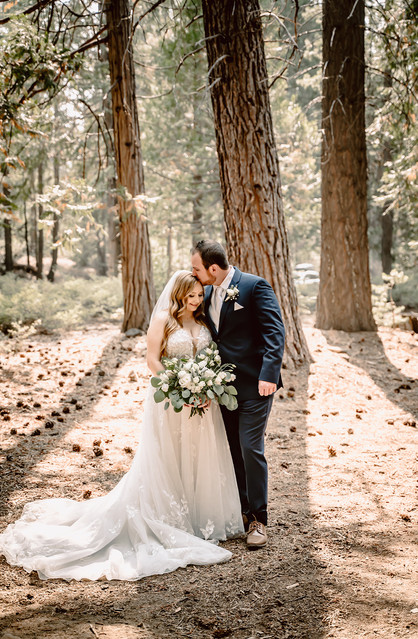 A wedding couple standing in the forest with the sun beams behind them