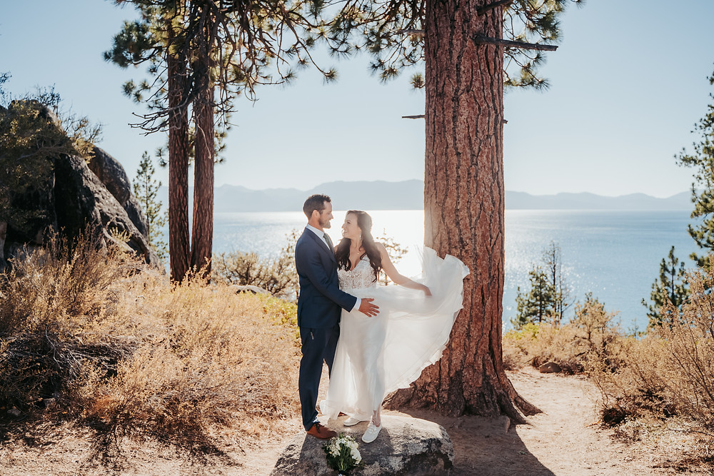 A bride with her dress flowing and the groom holder her standing on a rock during the Lagan Shoals Vista Point Elopement in Lake Tahoe.  One of the best places to elope in Lake Tahoe